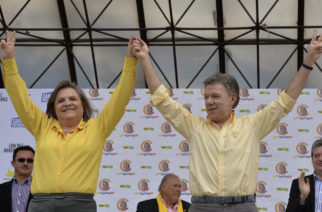 Colombia's President and presidential candidate Juan Manuel Santos (R) and Clara Lopez (L), former presidential candidate of the Alternative Democratic Pole party, raise their arms   during a campaign rallty in Bogota, on June 5, 2014. Santos, elected for the period 2010-2014, will run against the candidate of the Democratic Center party Oscar Ivan Zuluaga in the presidential run-off on June 15. AFP PHOTO/Diana Sanchez / AFP PHOTO / DIANA SANCHEZ